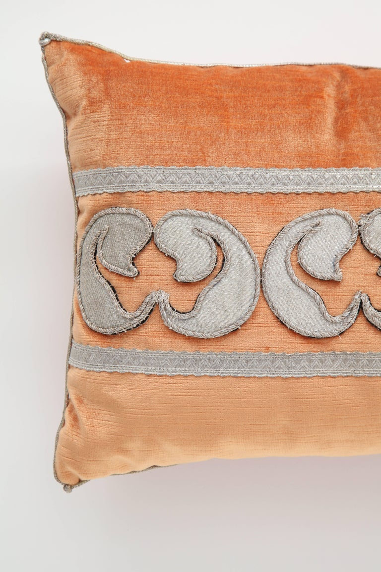 A stunning pillow in a tangerine velvet accented with antique metallic fragments forming a design between a border of antique metallic trim. Hand bordered in a metallic cording and down filled. Created by BViz Design.