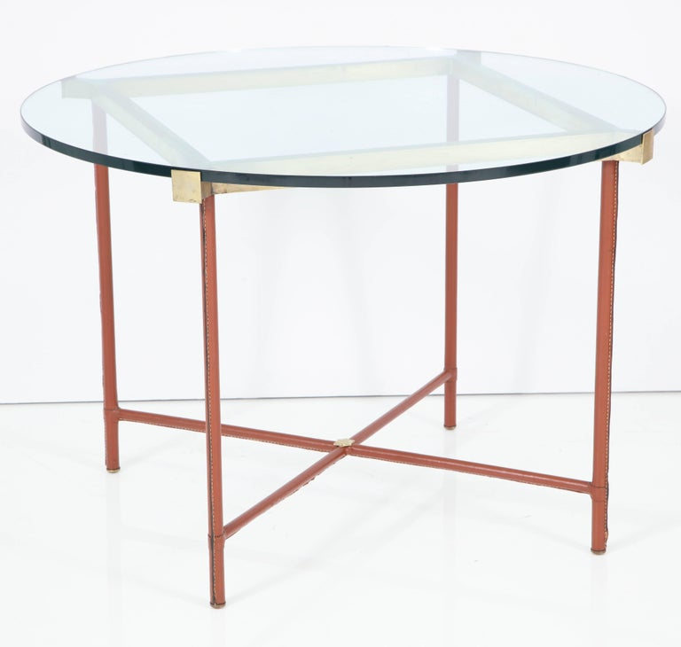 Elegant centre table by Jacques Adnet, metal frame covered in hand-stitched leather, brass hardware and frame. Glass top.