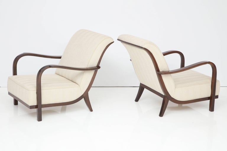 Walnut armchairs, newly finished and upholstered in linen. They have an Italy stamp and an illegible signature.