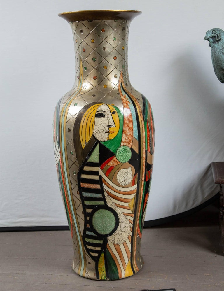 Painted in bright colors, possibly enamel. On a silver painted ground. Broken bits of egg shell (?) used to create some of the images in a mosaic form as seen clearly in the profile face. Gold colored lining. Unglazed bottom. No signature found.