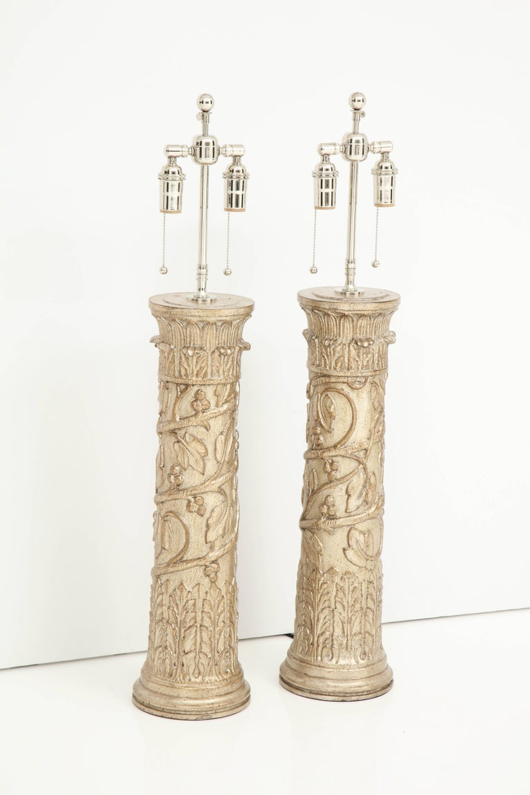 Pair of column lamps by James Mont. The lamps have a beautiful decorative design with a glazed silver leaf finish. They have been newly rewired for the US with polished nickel double clusters that take standard light bulbs.