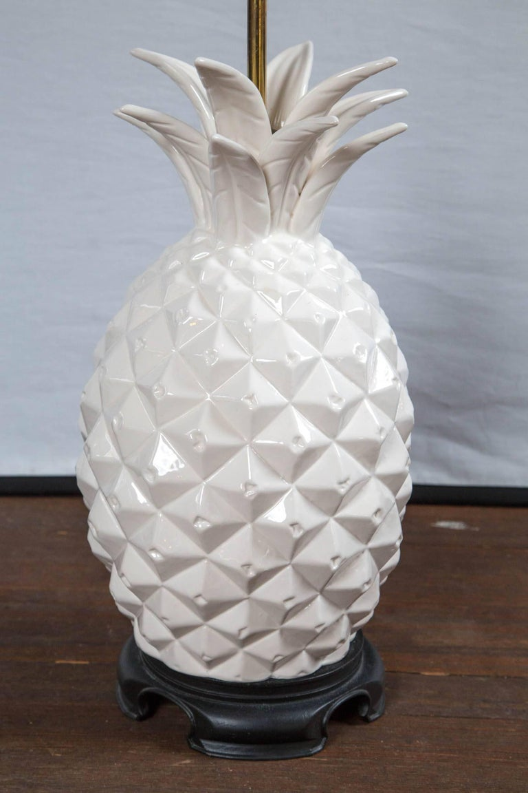 Large dynamic white ceramic pineapple lamp on carved wood base. 23