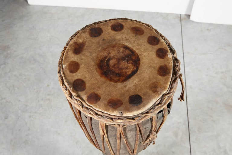 A 48 inch tall Primitive drum from the hill tribes on the border of Thailand and Burma with leather straps and original spotted hide top. A piece with great presence and history.