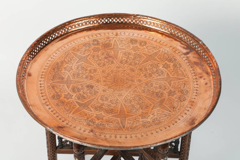 Moroccan antique copper tray table with wooden hand-carved Syrian folding base. The hammered copper tray is decorated with geometric Islamic Moorish designs. The top is removable and consist of a round Moroccan copper tray on a Middle Eastern