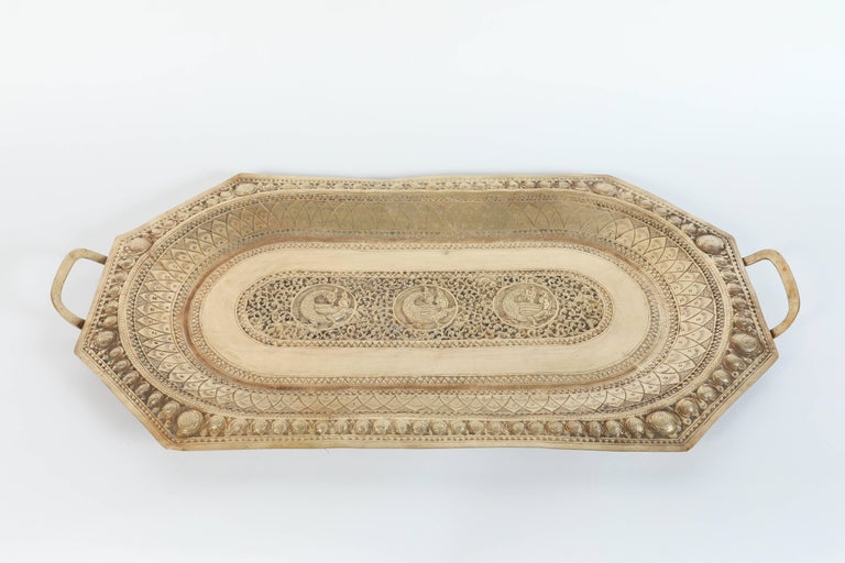 A large Mamluk revival Indo Persian brass charger serving tray with handles. Large octagonal serving tray engraved and finely decorated with peacocks and Moorish geometric designs. Repoussé floral and foliate motif to the oval tray with two peacock,