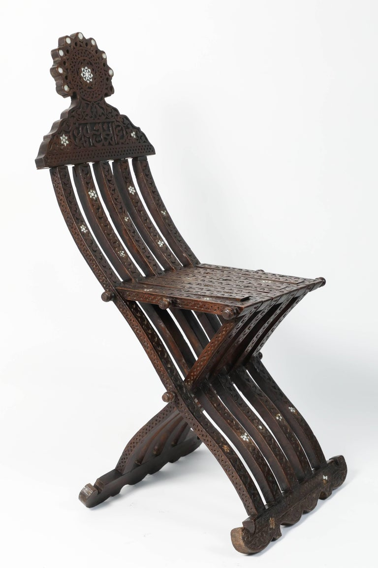 Middle Eastern Syrian wooden folding chair with intricate foliate carving and mother-of-pearl inlays.  Inlaid with mother-of-pearl stars and moon designs, hand-carved with Arabic calligraphy writing and foliages. Some mother-of-pearl inlay missing,