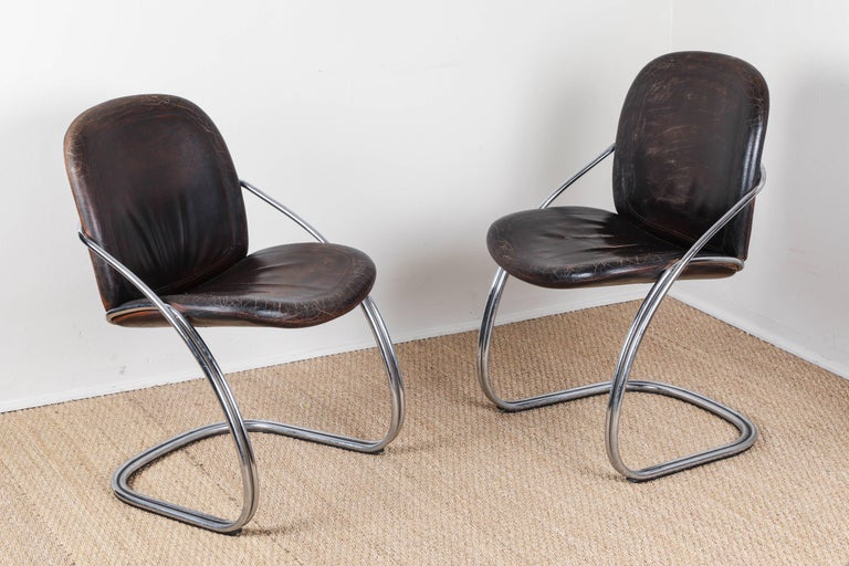 Ergonomic chrome chairs. Distressed dark brown leather seats and backs.   Offered by Pat McGann Gallery.