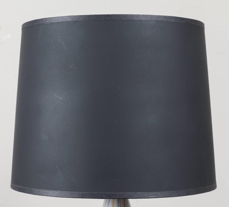 """A small painted ceramic table lamp with ebonized black wooden base. Updated and """"Americanized"""" hardware. Custom black paper shade with blue interior."""