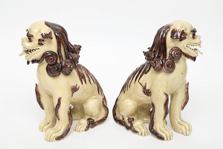 Lovely pair of cream and brown glazed Foo dogs made in Italy for Paul Hanson.