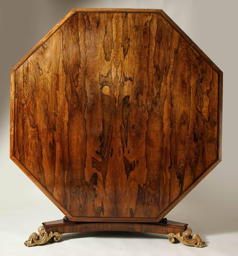 A very fine Regency rosewood centre table by Miles and Edwards, having an octagonal top with a molded edge over a parcel-gilt and carved rosewood pedestal ending in a tripartite base with gilt bronze acanthus leaf feet, the whole possessing vivid