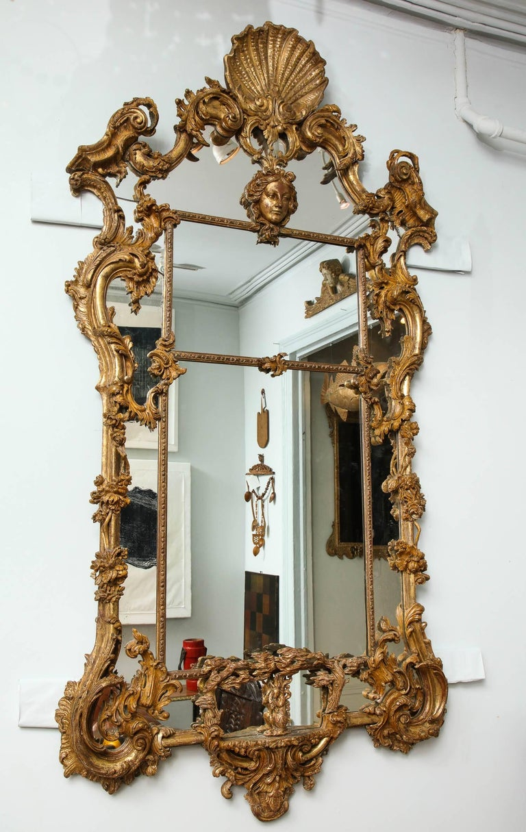 Fine George III style giltwood mirror in the manner of Thomas Johnson, the shell carved crest with foliate scrolled pediment, over a female mask, the sides with trailing flowering vines and scrolls, the lower border plate with central carving of a