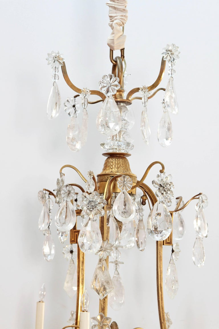 A large rock crystal and ormolu Louis XV style chandelier, nine (9) lights on three (3) tiers, with central post of ormolu and crystal, curving arms form a Greek key design with multiple large rock crystal drops  Sold in 1974 by Nesle, Inc. Fine