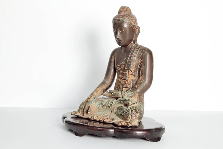 A figure of a 19th century seated Buddha in a meditative pose. Patinated bronze (with Verdigris) accented with colored glass as jewels.