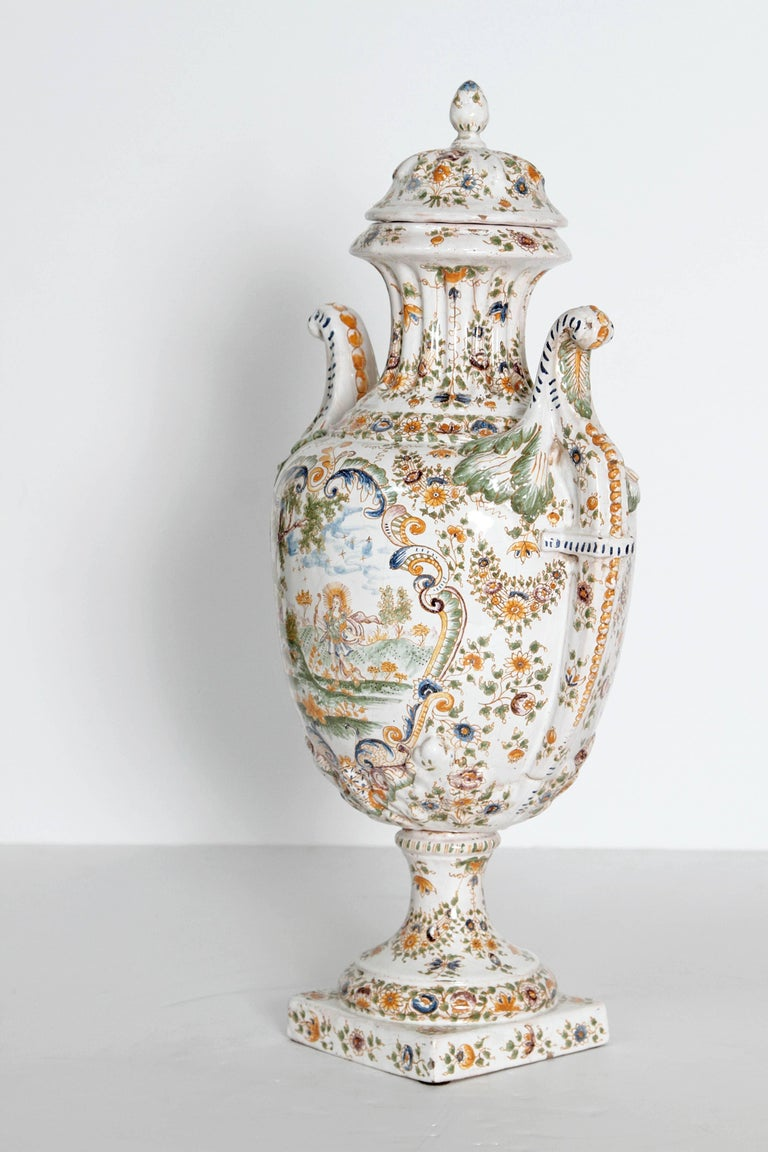 Large 18th century French faience lidded urn, white with yellow and blue floral decoration and scenic panels. All this rests upon a 5 inch square pedestal base with floral motif. Curved handles.