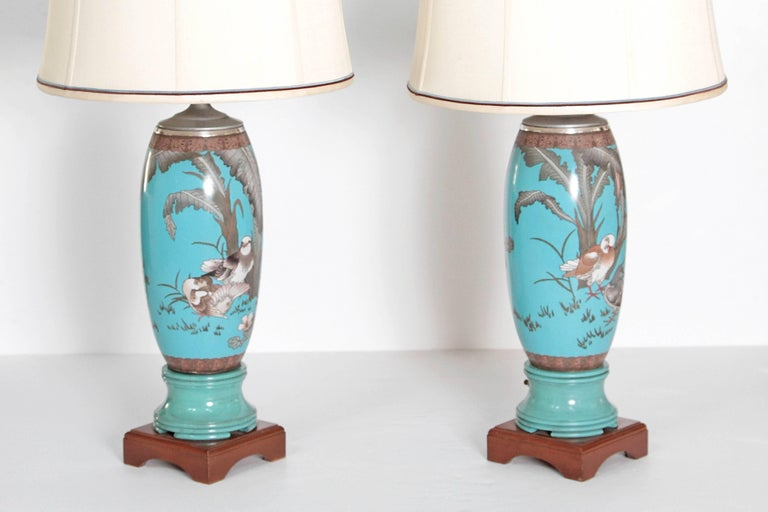 A pair of 19th century French cloisonne vases mounted as lamps. The body of the lamps are turquoise  with images of birds and foliage. Decorative 6 inch square bases.