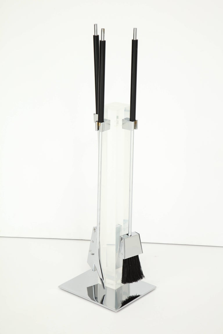 Decorative end iron, circa 1960. Made of polished chrome and Lucite.