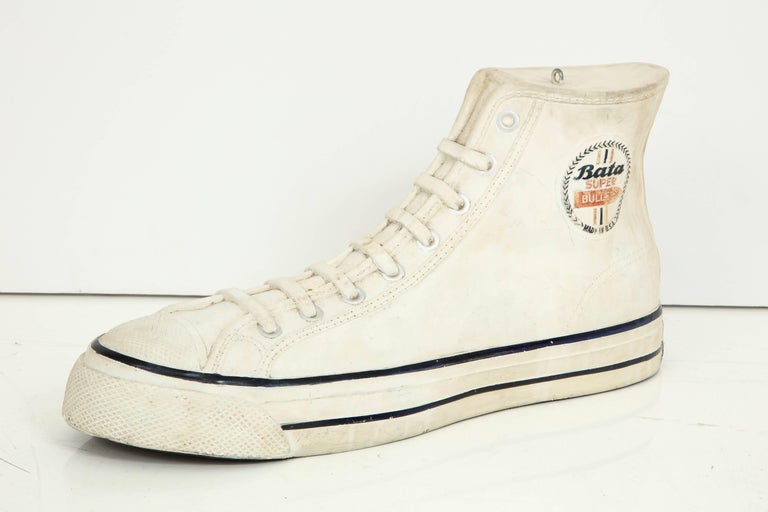 A large fully detailed Bata sneaker, looks like a Chuck Taylor style. The details extend to the sole who has the classic waffle pattern, mid-1970s.
