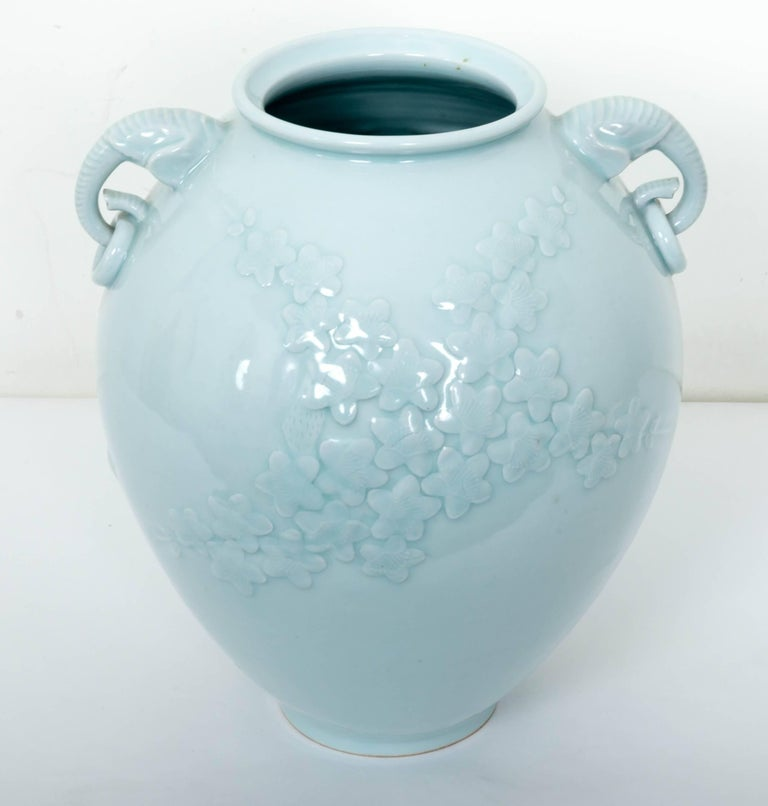 Large Chinese celadon porcelain vase elegantly crafted in a classic ovoid egg shape, with raised floral relief design and unique elephant head handles, makes this an important decorative statement for a home or business. In Chinese art, the elephant