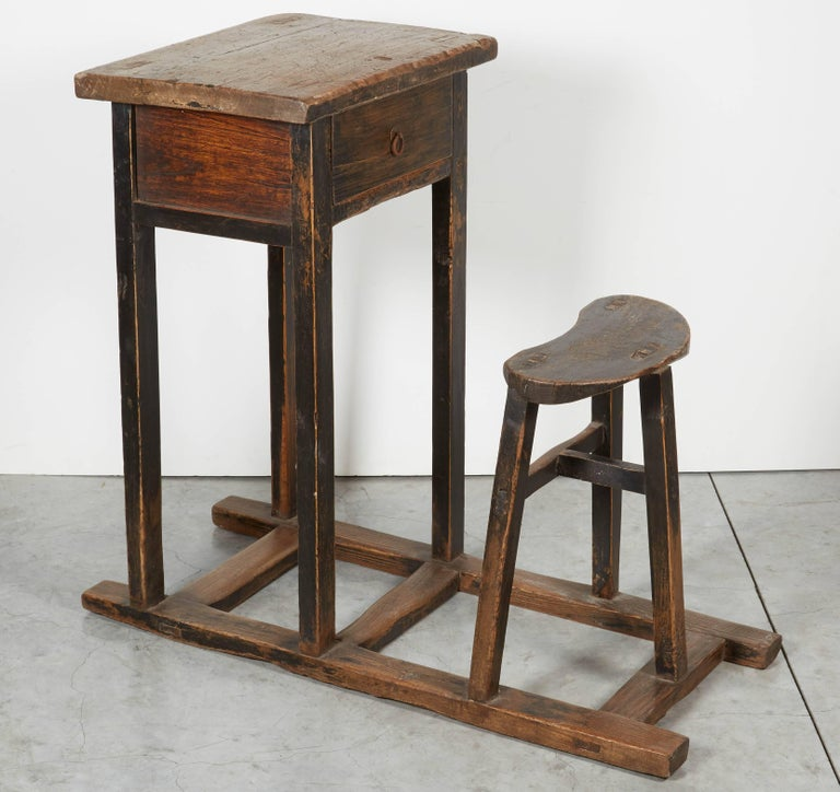 A nicely worn antique Chinese school desk with simple stool and single drawer all in one piece. Great patina with traces of original black paint. From Shanxi Province, circa 1900. D305.