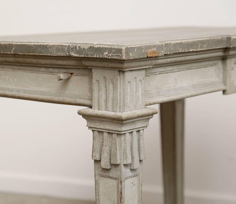 Antique Swedish period Gustavian painted console table early 19th century distressed painted on top in a darker grey with original scratches, cracks and marks and layers of original paint. Apron adorned with rectangular ornaments carving around