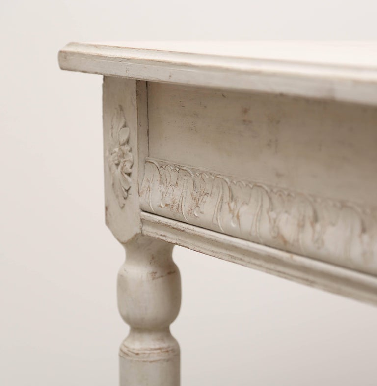 Pair of antique Swedish painted console tables Gustavian style, late 19th century both with profiled aprons and carved with borders and rosettes on square rounded fluted legs. They have been refreshed with Gustavian ivory/ white distressed paint