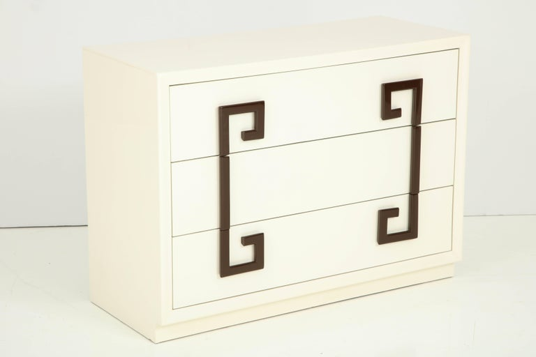 Hollywood Regency chest of drawers in a sophisticated Ivory lacquer with contrasting stylized Greek key pulls in a chocolate brown lacquer.