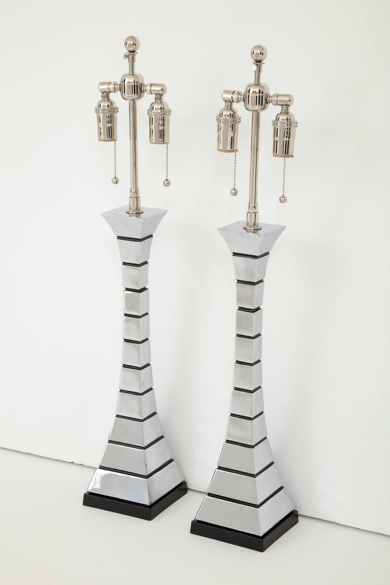 Pair of 1970s midcentury polished chrome lamps. The lamps have a wonderful Eiffel Tower feel to them with a subtle hour glass shape which is alternated by painted black horizontal channels. The lamps have been newly rewired for the US with