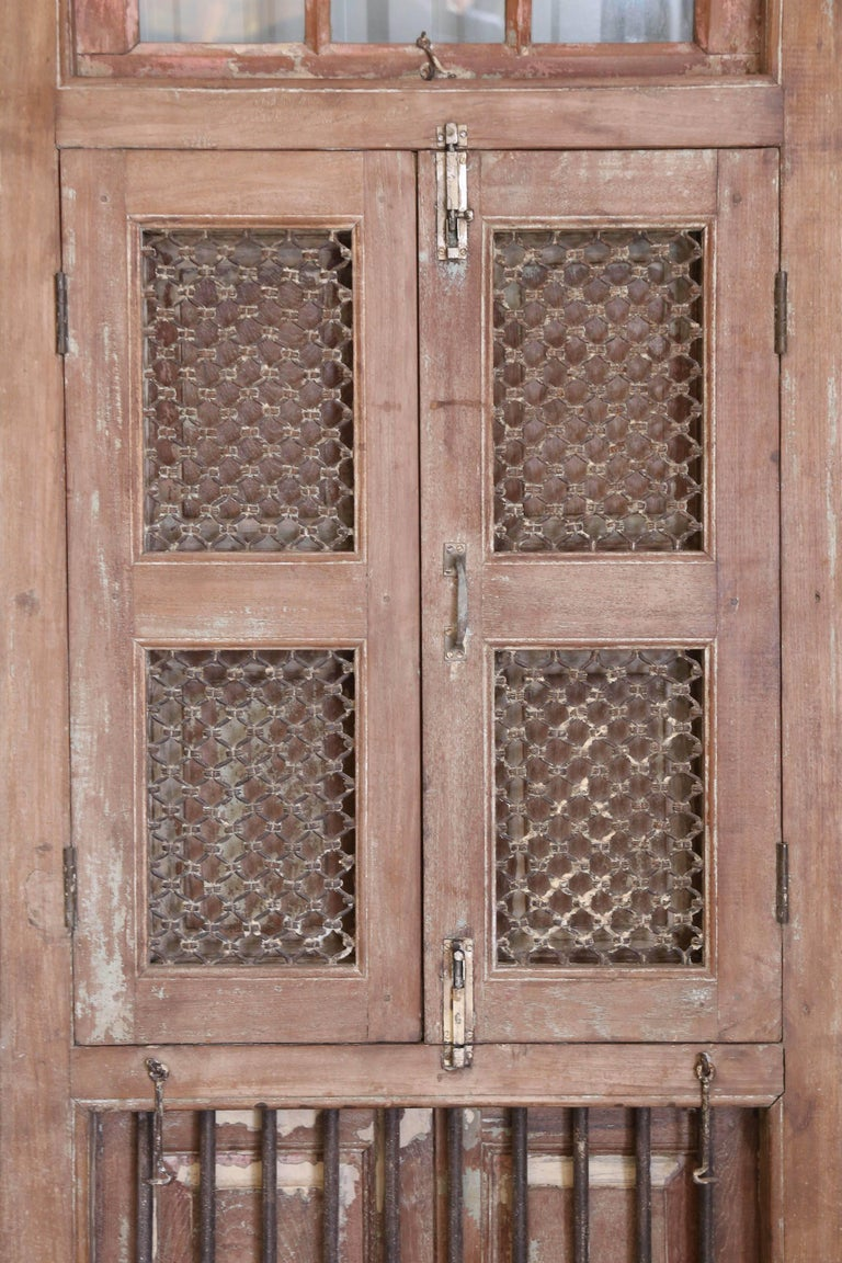 This elaborate solid teak wood window with intricately hand forged iron works comes from a Portuguese colonial church built in west coast of India in the early 19th century. It is made of solid teak wood with hand forged iron bars and iron screen.
