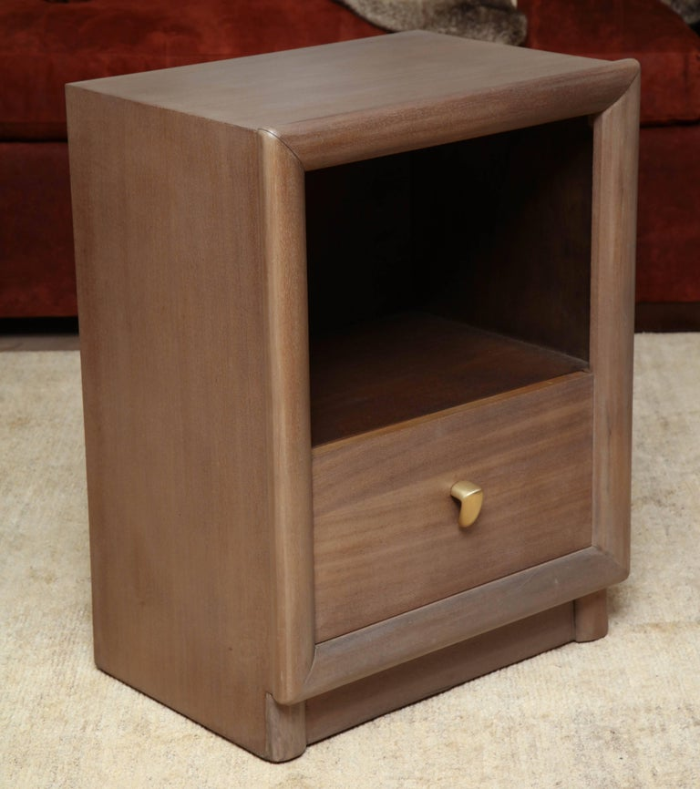 Pair of dark walnut and faun-finished walnut nightstands with brass finger pulls in the manner of Robsjohn-Gibbings, circa 1950.