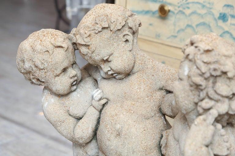 19th century French cast stone statue of three putti.