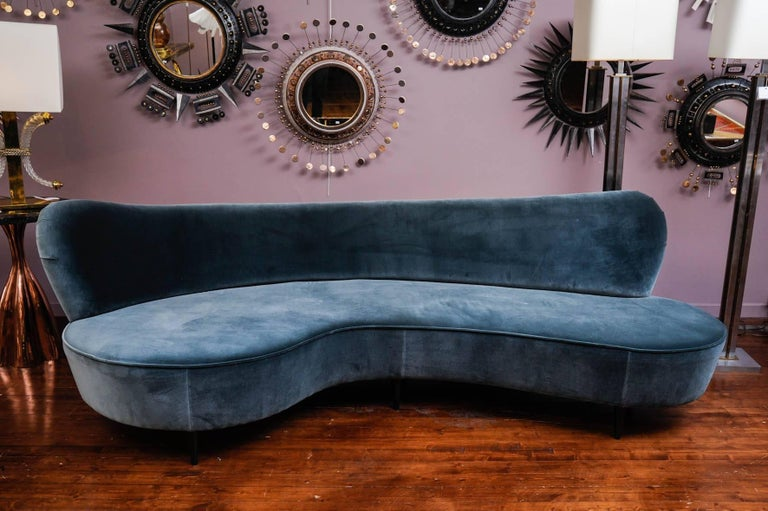 Curved vintage sofa, with six wood legs.