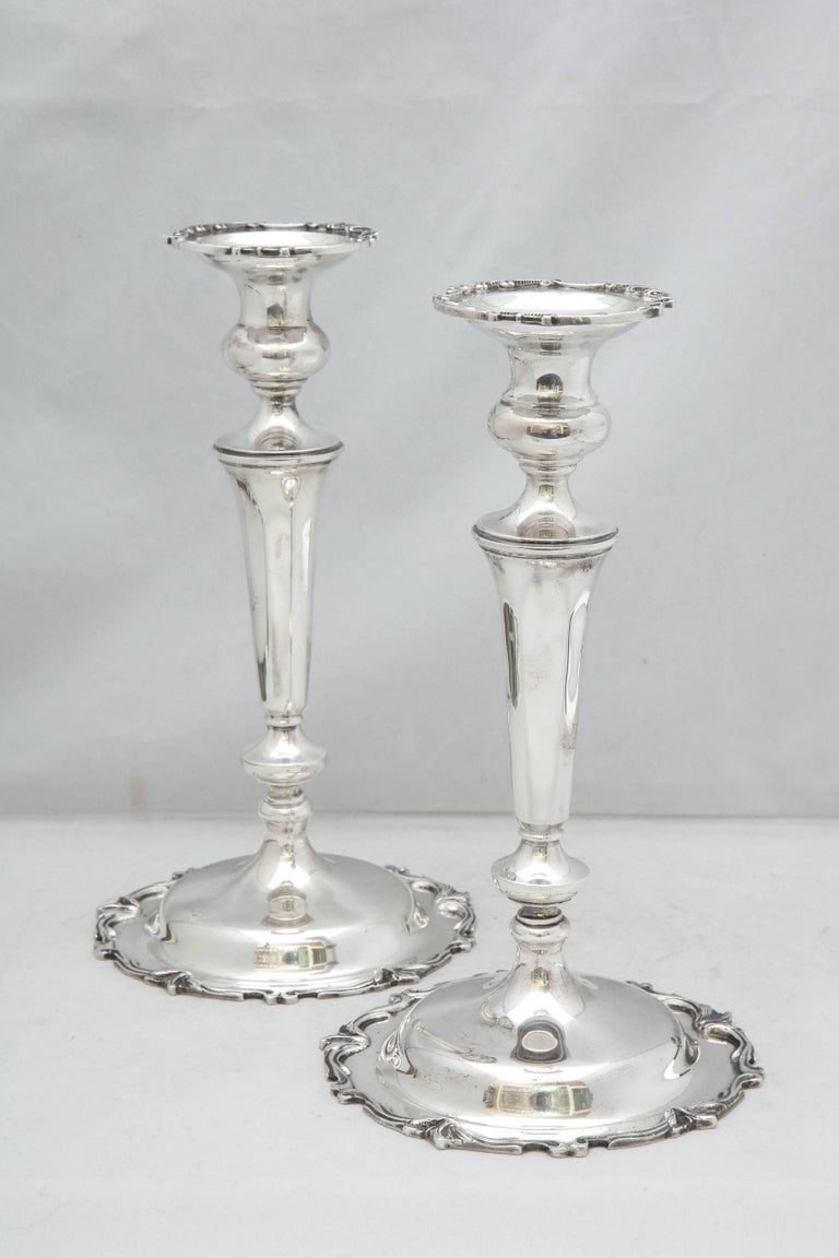 Pair of tall, sterling silver, Edwardian style candlesticks, Michael C. Fina Co., New York, circa 1930s. Measure approximately 10 1/8 inches high x over 5 1/2 inches in diameter across base of each. Design on edge of base of each is continued on