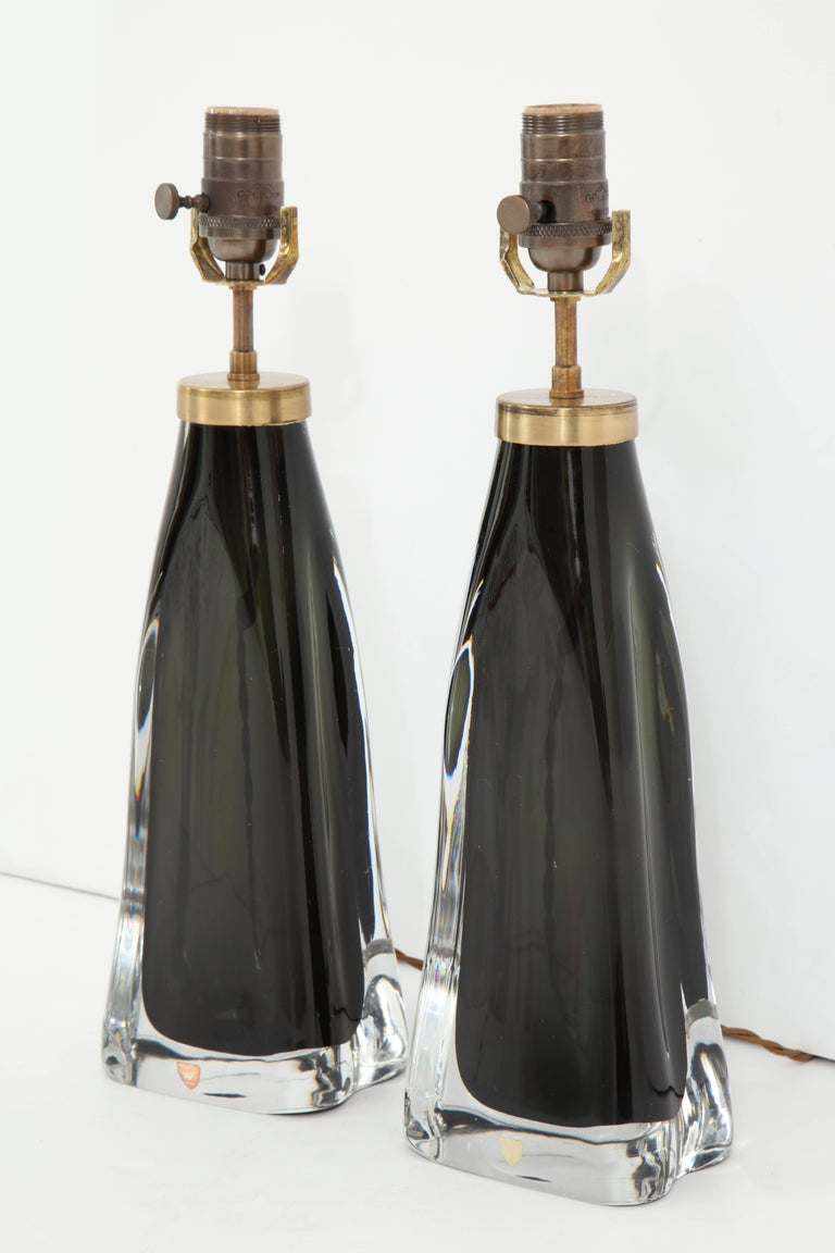 A pair of crystal lamps produced by Orrefors, Sweden, in a stunning midnight blue. The lamps have been recently re-wired for use in the U.S. and have brass fittings with cloth cords. Height listed is to bottom of harp.