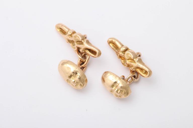 Theatrical mask cufflinks in solid 18k gold attached by small link chains to shaped bar links of foliate design.  Late 19th century.   Masks-1/2 in. (1/3 cm.) long; bar links-3/4 in. (1.9 cm.) long; distance between links: ¾ in. (1.9 cm.)  An