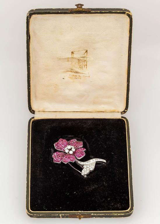 Beautiful brooch by VAN CLEEF & ARPELS with FRENCH hallmarks, finely crafted in 18k white gold with invisible set rubies weighing a total of approximately 40.00 carats and diamonds weighing approximately 3.50 carats in total.  Circa 1930's