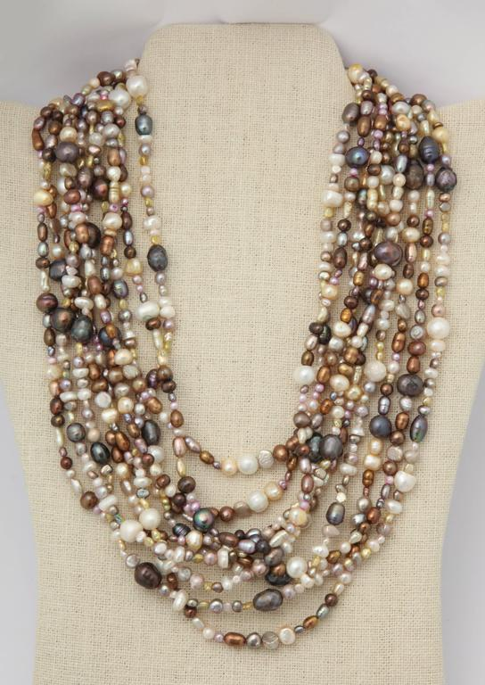 This necklace is 10 strands of graduated lengths of multicolored fresh water pearls. The shortest strand is 18 1/2 and the longest 23.5 in. The silver bayonet clasp is handmade with a beautiful scroll design and a figure 8 safety on each end. This