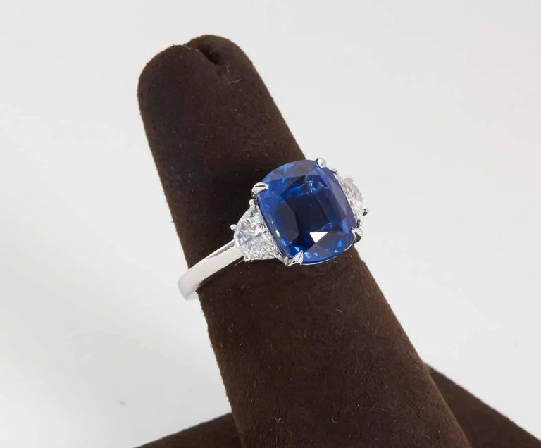 A beautiful sapphire and diamond ring! The perfect size, color and shape!  5.54 carat cushion cut vivid blue sapphire.  0.43 carats of white side diamonds, custom platinum mounting.  The sapphire is accompanied by a C. DUNAIGRE of