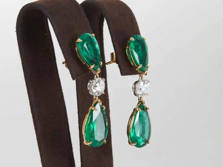 A beautiful pair of handmade Green Emerald and Diamond drop earrings.   4 pear shape Green Emeralds with fine color and brilliance weigh 13.22.  2 round brilliant cut white diamonds weigh 1.67 cts.  18k yellow and white gold.