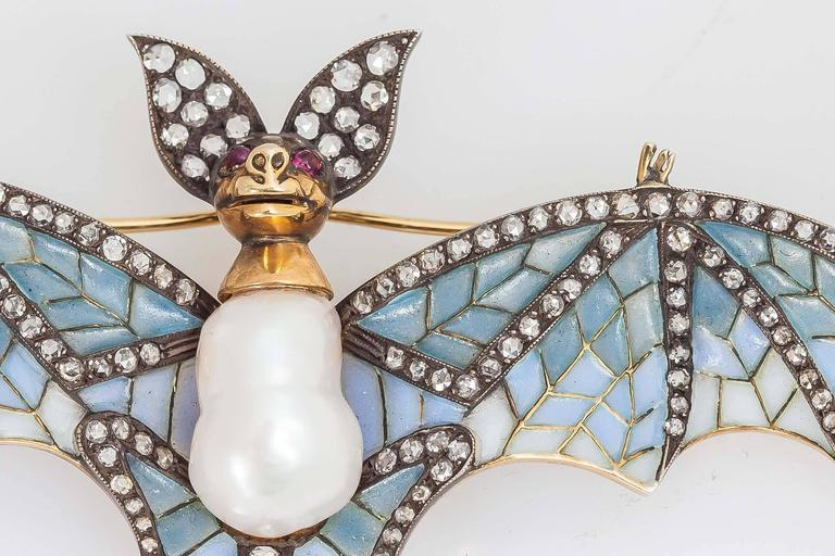 Beautiful bat brooch finely crafted in 18k yellow gold and silver with light blue plique a' jour wings and round brilliant cut diamonds weighing approx. 2.00 carats and baroque pearl body and ruby ayes.