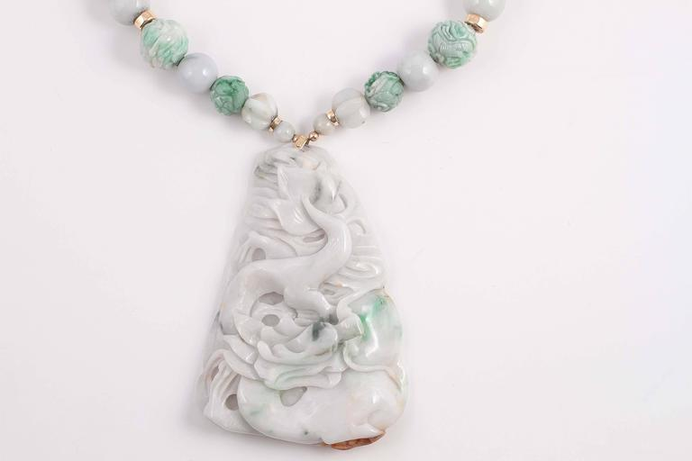 Boldly and artfully carved jade pendant suspended from polished and carved jade beads. A testament to the craftsmen from the East.