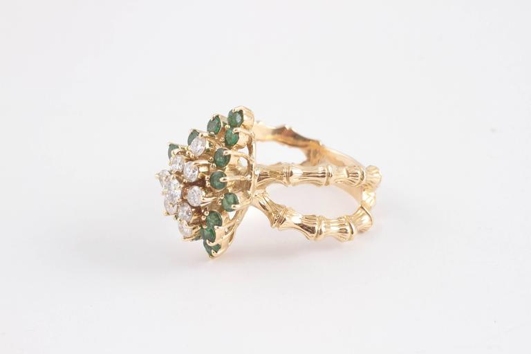 18 karat yellow gold bamboo style double shank set with a marquise shape cluster of diamonds surrounded by emeralds.  A fun and fanciful feel to the whole ring.  Size 9 1/2