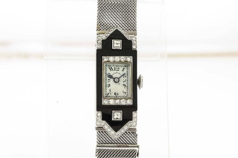 Platinum Patek Philippe & Cie, Genève, for Tiffany & Co, circa 1924, is a fine Art Déco, platinum,  diamonds and onyx rectangular,women's wristwatch with platinum and diamond mesh band. The 13mm x 30mm platinum hinged case, is decoratively
