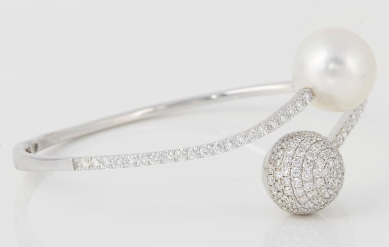 18K White gold bypass bangle bracelet featuring one South Sea Pearl measuring 12-13 mm and numerous round brilliants weighing 2.80 carats.  Color G-H Clarity SI Pearl Quality: AA  Pearl can be changed upon request. Price subject to change.