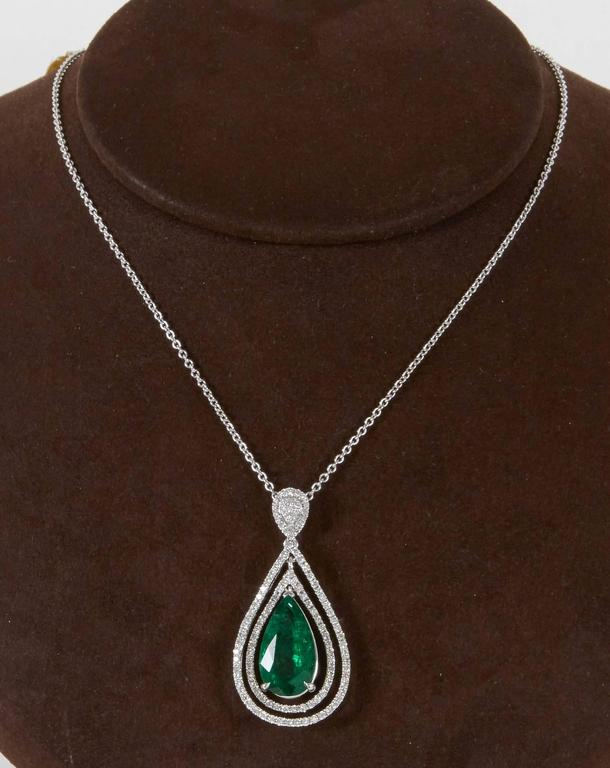 A beautiful green emerald and diamond pendant.   5.50 carat certified pear shape Green Emerald   1.48 carats of white round brilliant cut diamonds   18k white gold   The pendant hangs from a 16 inch 18k white gold chain