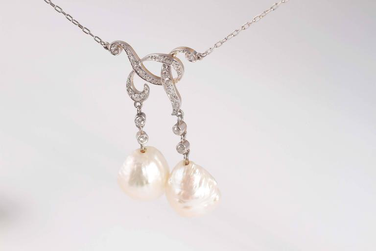 Complete with a GIA report stating that the pearls are natural, this necklace is circa 1900 and is both eye-catching and unique.  0.42 carats of diamonds.