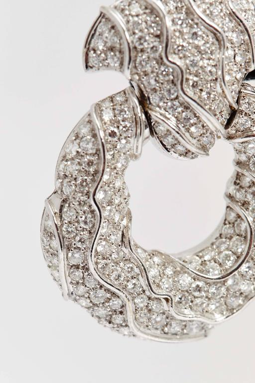 A pair of impressive ear pendants of undulated design, with fine quality brilliant cut diamonds mounted on 18kt white gold. Made in Geneva, by Jahan, circa 1980.