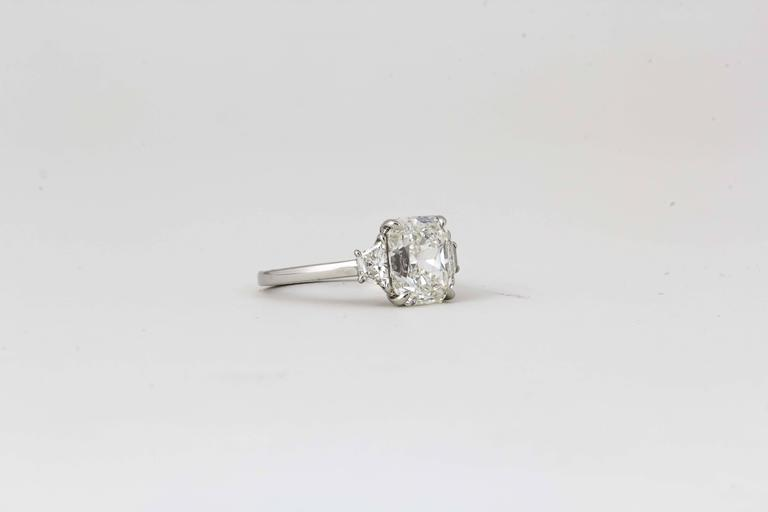A beautiful radiant cut diamond set in a timeless custom made mounting.   3.18 carat center H VS1 Radiant cut diamond set with matching trapezoid cut diamonds weighing .37 cts. Set in a custom platinum mounting.   This ring is currently a size
