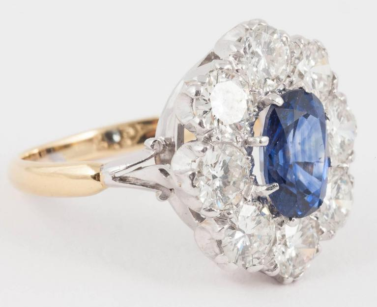 This natural Ceylon Sapphire ring surrounded by Diamonds set in 18ct White and yellow 18ct Gold from the 1940's  Ring size L