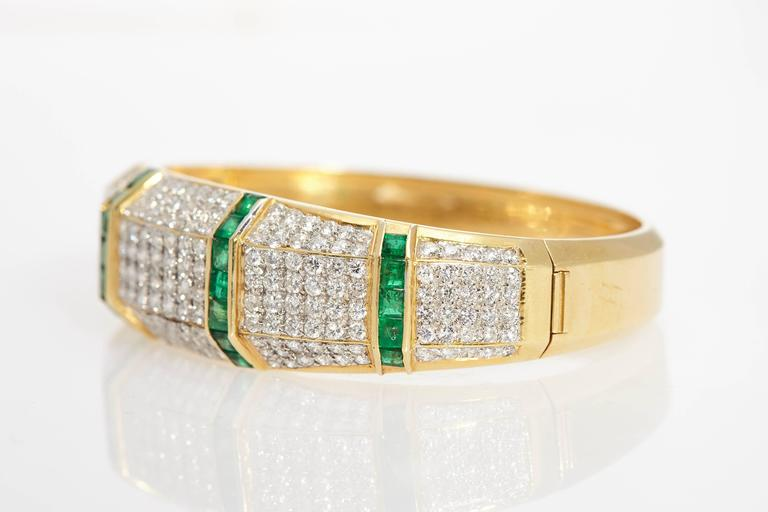 A fine brilliant cut diamond and squared cut emerald bangle bracelet. Made in Italy, circa 1970.