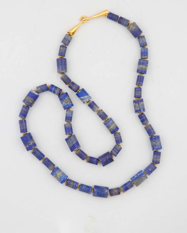 A lapis lazuli bead necklace composed of carved lapis lazuli tube beads and  18kt yellow gold rondelles. The necklace has an 18kt yellow gold trumpet clasp. Length: 28.5 inches